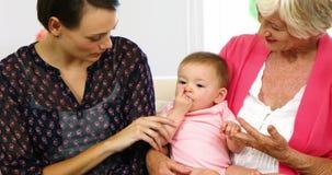 Meninas da família que senta-se no sofá com o bebê video estoque