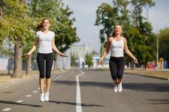 Meninas da ginástica com cordas de salto em um fundo do parque Ostenta amigos Conceito ativo da juventude fotos de stock royalty free