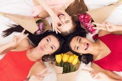 Meninas da vista superior três que encontram-se na cama com flores Estão comemorando mulheres ` s dia o 8 de março fotos de stock royalty free