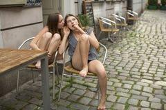Meninas das amigas que bisbilhotam ao sentar-se em um café da rua Fotos de Stock