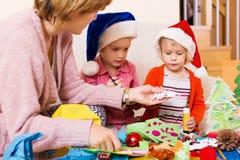 Meninas de ajuda da mulher para fazer a decoração para o Xmas Foto de Stock Royalty Free