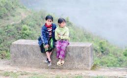 Meninas de Hmong que sentam-se na estrada rural na cidade de Sapa, Vietname do norte Foto de Stock