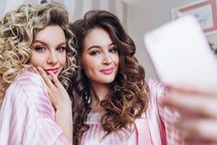 Meninas de partido Galinha-partido Duas moças tomam um selfie para seu blogue em um telefone esperto em pijamas cor-de-rosa fotografia de stock royalty free