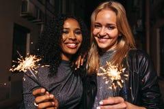 Meninas de sorriso com os chuveirinhos que olham a câmera imagem de stock royalty free
