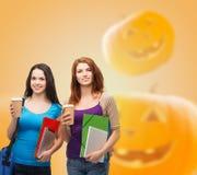 Meninas de sorriso do estudante com livros e os copos de papel Imagem de Stock Royalty Free
