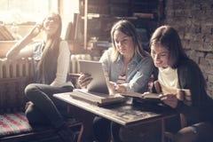 Meninas de sorriso felizes na biblioteca que senta-se junto e que estuda Foto de Stock Royalty Free