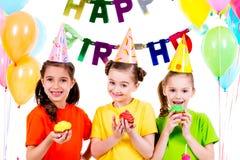 Meninas de sorriso felizes que guardam bolos coloridos Fotos de Stock