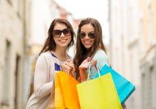 Meninas de sorriso nos óculos de sol com sacos de compras Fotografia de Stock Royalty Free