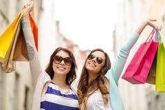 Meninas de sorriso nos óculos de sol com sacos de compras Imagens de Stock