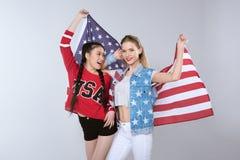 Meninas de sorriso novas que estão e que guardam a bandeira dos EUA isolados no cinza Imagens de Stock Royalty Free