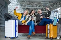 Meninas de sorriso que fotografam-se em telefones celulares no terminal Imagem de Stock Royalty Free