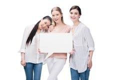 Meninas de sorriso que mantêm a bolha vazia do discurso isolada no branco Imagem de Stock Royalty Free