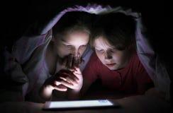 Meninas de sorriso que surfam a tabuleta sob a cobertura na noite fotografia de stock royalty free