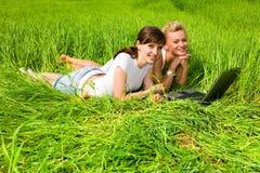 Meninas de Tho que riem perto do computador portátil ao ar livre Fotos de Stock Royalty Free