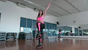 Meninas desportivas que treinam no gym com sapatas do kangoo filme