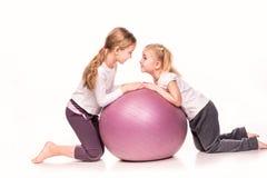 Meninas desportivos em uma bola do ajuste isolada sobre o branco Imagem de Stock Royalty Free