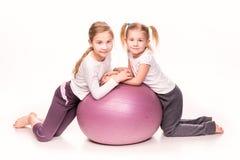 Meninas desportivos em uma bola do ajuste isolada sobre o branco Imagens de Stock Royalty Free