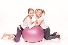 Meninas desportivos em uma bola do ajuste isolada sobre o branco Imagens de Stock