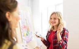 Meninas do estudante com pintura da armação na escola de arte Foto de Stock Royalty Free