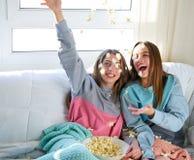 Meninas do melhor amigo no sofá que tem o divertimento com pipoca imagens de stock royalty free