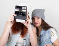Meninas do moderno da beleza pretas e vermelhas nos óculos de sol, fazendo a foto em instantâneos da câmera careta dos adolescent foto de stock royalty free