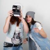 Meninas do moderno da beleza pretas e vermelhas nos óculos de sol, fazendo a foto em instantâneos da câmera careta dos adolescent fotos de stock royalty free