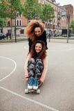 Meninas do moderno que montam em skates ao longo da estrada Fotos de Stock