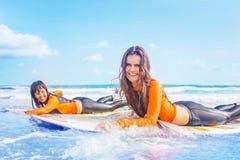 Meninas do surfista que treinam no oceano imagem de stock