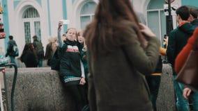 Meninas do turista na ponte que toma o selfie no smartphone em horas de ponta da cidade video estoque