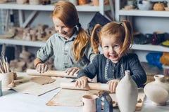 Meninas doces ruivos alegres com o pino do rolo que senta-se na tabela foto de stock royalty free