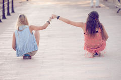 Meninas dos adolescentes do verão que sentam-se em skates imagens de stock royalty free