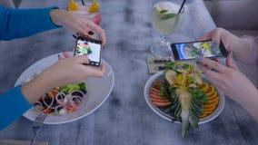 Meninas dos vegetarianos que tomam a foto de comer delicioso no telefone celular para redes sociais durante o almoço saudável no  vídeos de arquivo