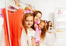 Meninas durante a compra que escolhe o couro cru atrás dos vestidos Foto de Stock Royalty Free