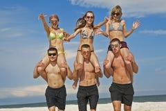 Meninas e indivíduos na praia Imagens de Stock