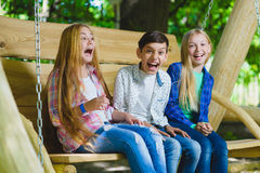 Meninas e menino de sorriso que têm o divertimento no campo de jogos Crianças que jogam fora no verão Adolescentes em um balanço Fotos de Stock