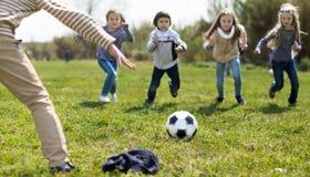 Meninas e menino que jogam o futebol no parque no outono fotografia de stock
