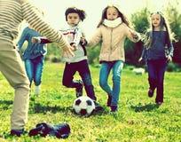 Meninas e um menino que joga o futebol no parque no outono fotos de stock