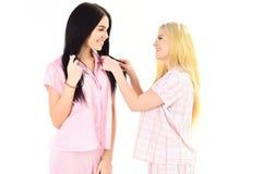 Meninas em pijamas cor-de-rosa, fundo branco isolado Louro, morena nas caras de sorriso na roupa para o olhar do sono bonito Imagens de Stock