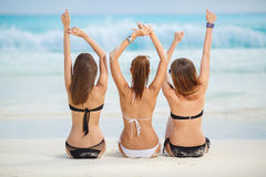 Meninas em tomar sol dos biquinis, sentando-se na praia Imagem de Stock Royalty Free