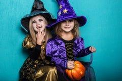 Meninas em um terno de uma bruxa Halloween fairy tale Retrato do estúdio no fundo azul imagem de stock