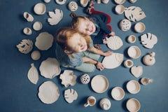 Meninas engraçadas com os olhos fechados que sentam-se no assoalho com muitos produtos da argila foto de stock royalty free