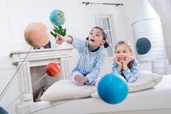 Meninas entusiasmado que olham modelos dos planetas Foto de Stock
