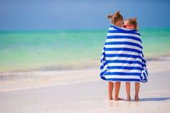 Meninas envolvidas na natação do arter de toalha na praia tropical Imagem de Stock