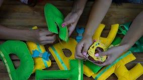 Meninas feitos a mão que costuram letras do feltro filme