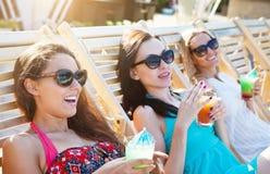 Meninas felizes com as bebidas no partido do verão Foto de Stock