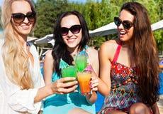 Meninas felizes com as bebidas no partido do verão Fotos de Stock