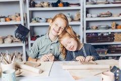 Meninas felizes com os olhos fechados que sentam-se na lição das artes e dos ofícios foto de stock