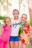 Meninas felizes com pintura da arte da cara no parque Foto de Stock Royalty Free
