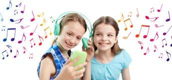 Meninas felizes com smartphone e fones de ouvido Imagem de Stock Royalty Free