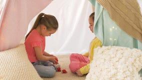 Meninas felizes na barraca das crianças que joga o tea party em casa filme